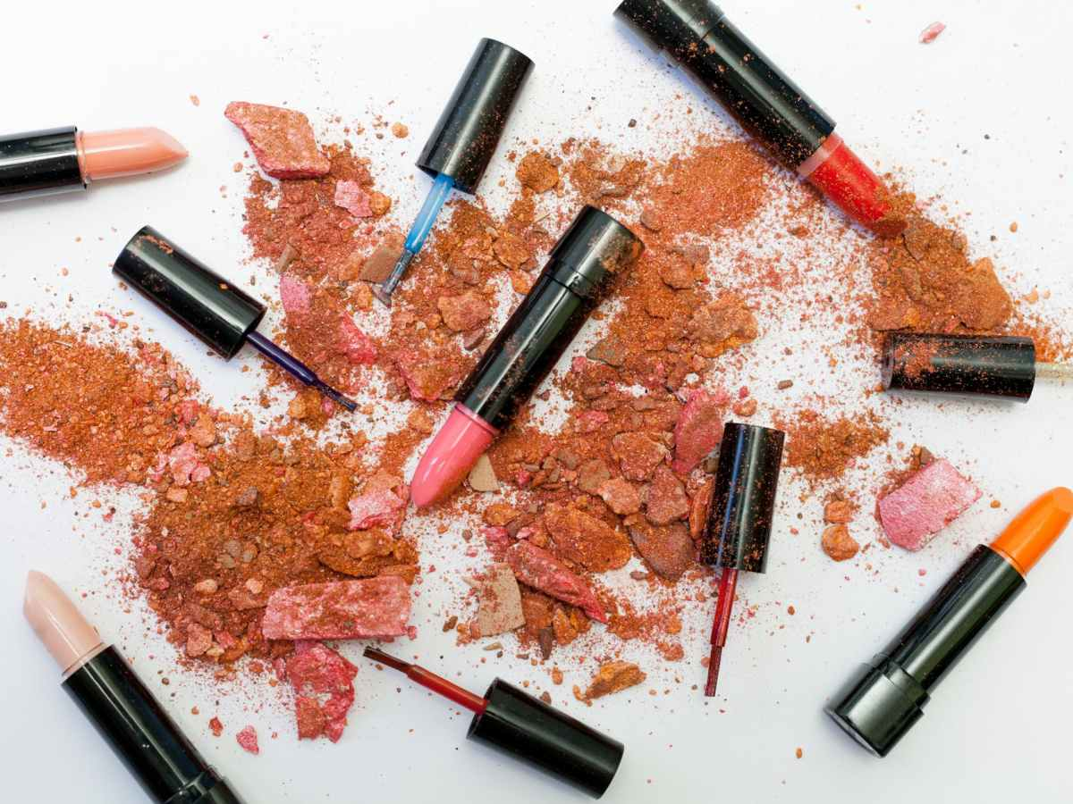 Smashed make powders on a white background. The smashed me up covers red, pink orange and 2 nude lipsticks as well as red, blue and clear nail polish brushes.