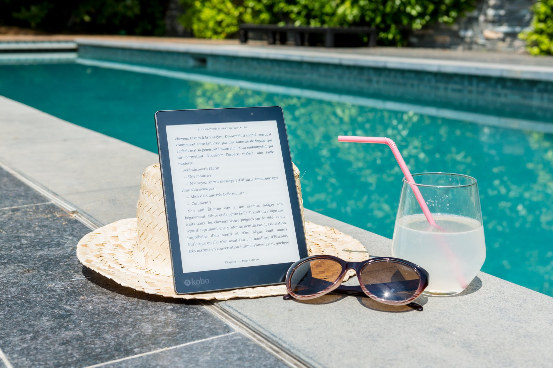 A picture by the pool with as kindle on a straw hat, with sunglasses at the side and a clear drink with a pink straw in it.