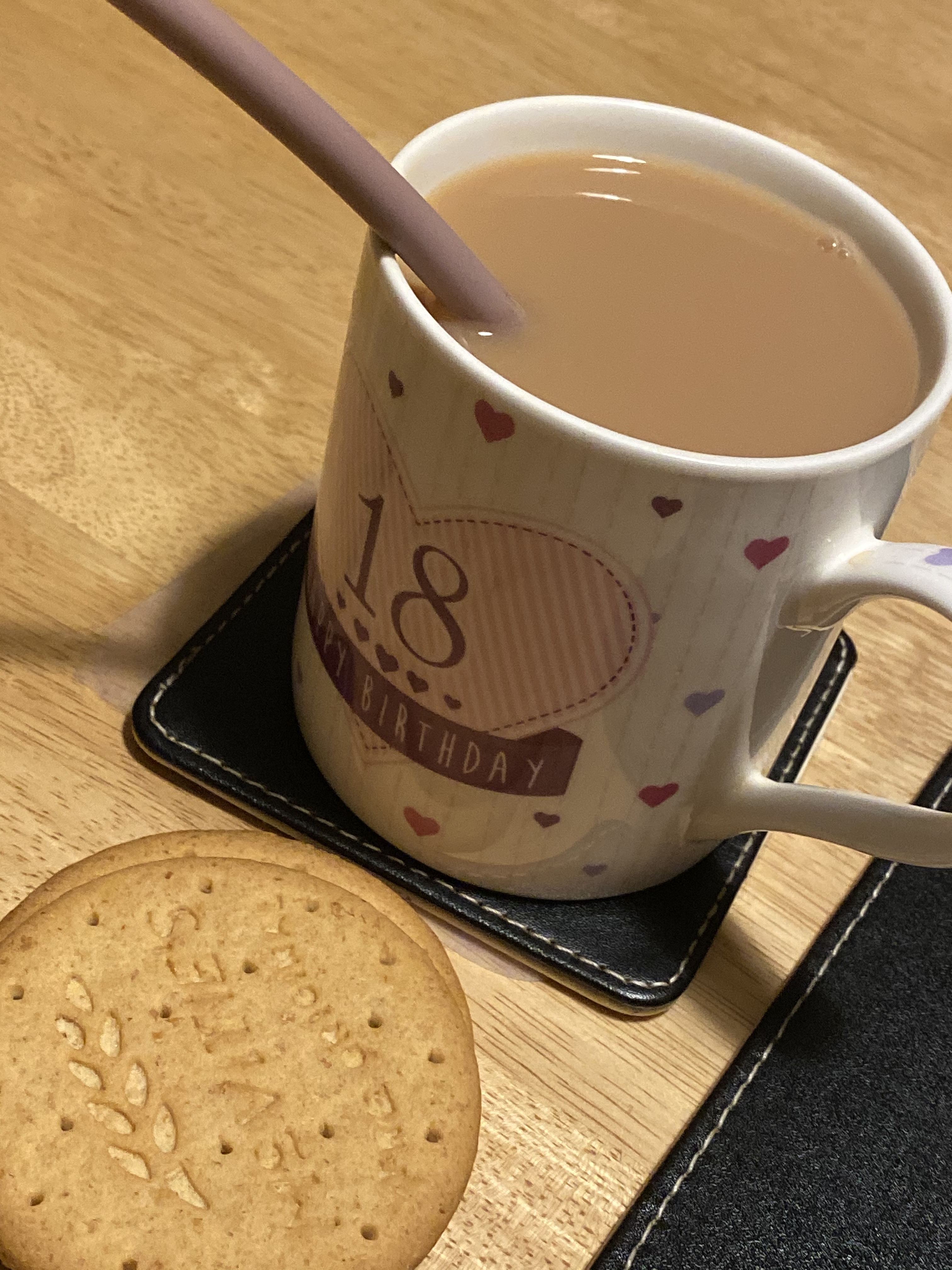 2 digestive biscuits with a a cup of tea, with a brown straw. This is on a black placemat on an oak table. The cup has small love heart with 18 in a big love heart and reads 'Happy Birthday' on a purple banner.