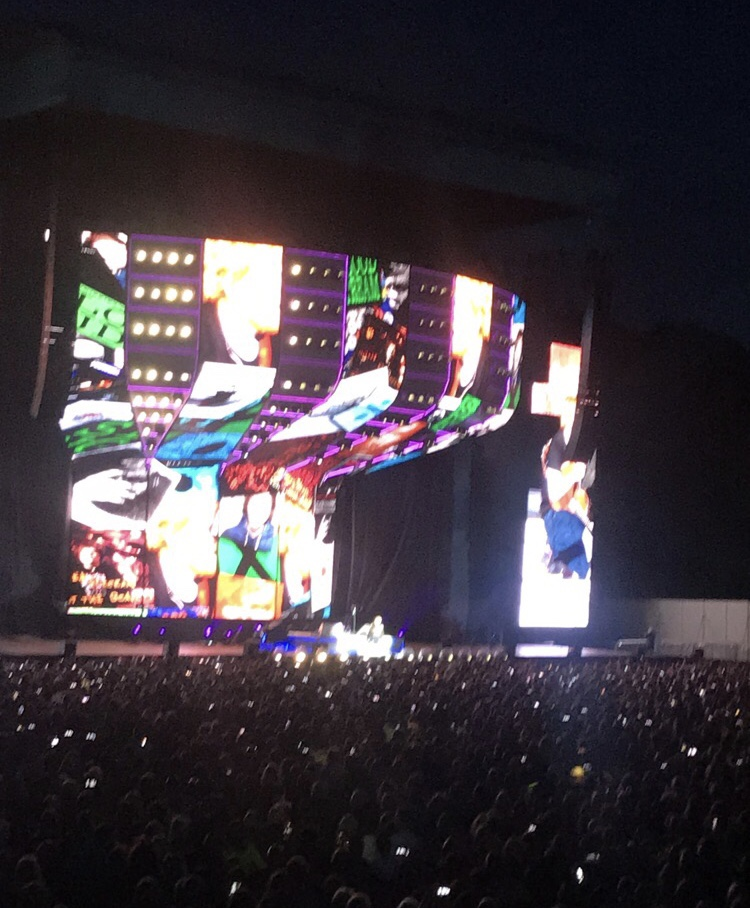 A photo of an Ed Sheeran Concert, you can see the crowd in front of me and the stage. The screens on the stage show ask his records.