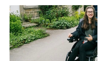 A photo of myself with a very big grin in my wheelchair going toward to camera. I have my glasses on, a green jumper and my hair in half and half. I am on a path and to the left there is some small bushes against a stone wall.
