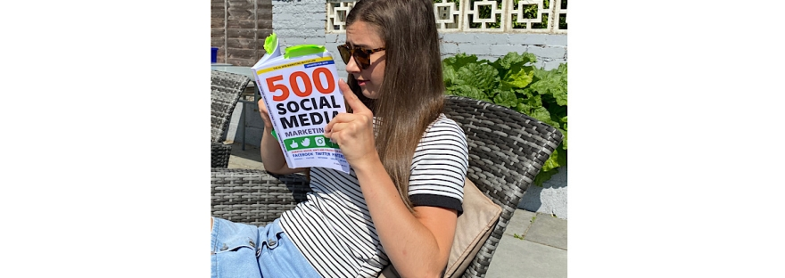 Sat in one the garden patio on outdoor furniture reading a book named '500 Social Media Tips' I have a white top on with black stripes with and light blue denim skirt with buttons down it.