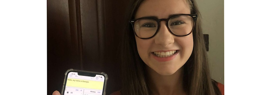 """Myself in my glasses with a big girl holding up my phone showing my text to speech communication app. Written in the app in a yellow box is """"Hello my name is Georgia""""."""
