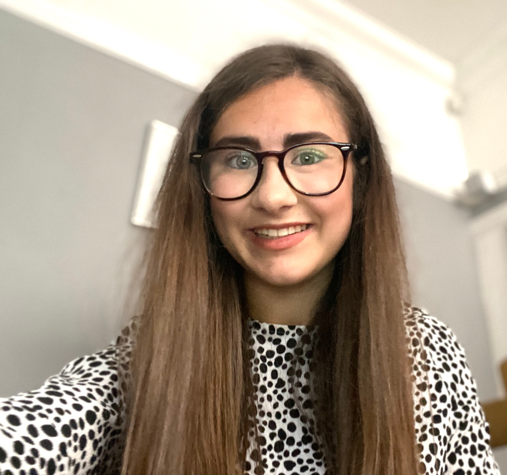 A selfies style photo of myself in a white blouse with black spots. I have straight hair and am wearing my glasses. The background is half grey and white