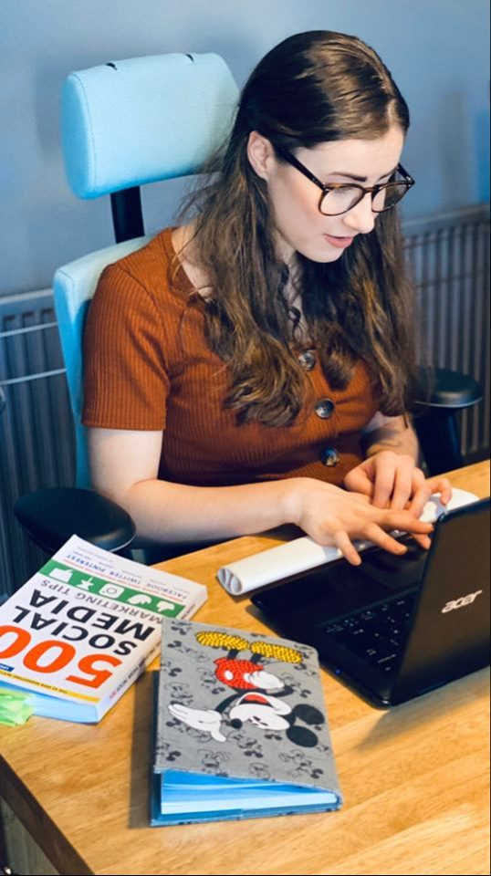 Myself sitting in my blue chair looking at my laptop with a Disney Micky Mouse notebook and a social media tip book with 500 tips. I have a brown top on with buttons my hair is down and I have my glasses on. The background is grey.