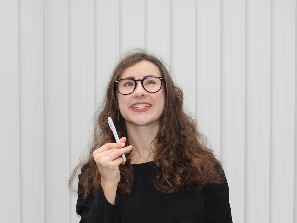 Myself in a plain black long-sleeve blouse with curly hair and my glasses on holding a plain white pen and smiling looking up in thought. The background is light grey vertical blinds.
