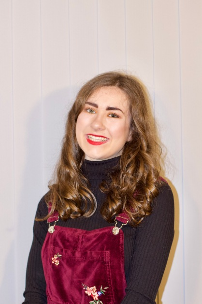 A photo of myself with curly hair. I am against grey vertical material blinds. I have my make up done with brown/gold eyeshadow and bright red lipstick. I have a black polo neck on, and a burgundy dungaree dress that is velvet like material with flowers. You can see my shadow against the vertical blinds.